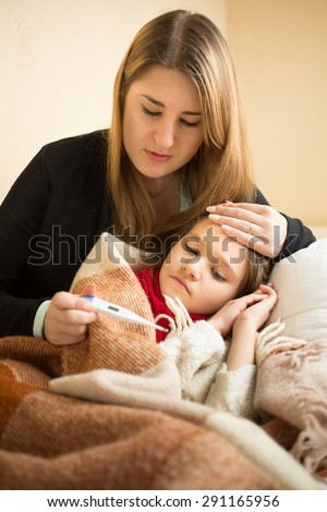 Portrait of caring mother measuring sick daughter temperature with digital thermometer - stock photo