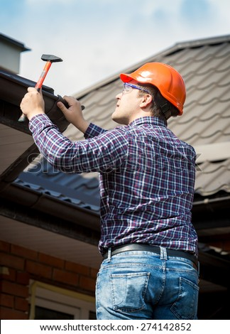 Portrait of carpenter at work repairing house roof - stock photo