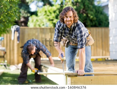 Portrait of carpenter cutting wood with saw while coworker drilling in background at construction site - stock photo