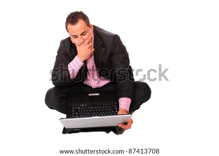 Portrait of casual businessman sitting on floor with laptop on white background - stock photo