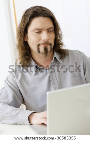 Portrait of casual businessman working at desk using laptop computer, looking at screen. - stock photo