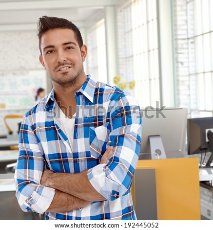 Portrait of casual man at office, looking at camera smiling. - stock photo