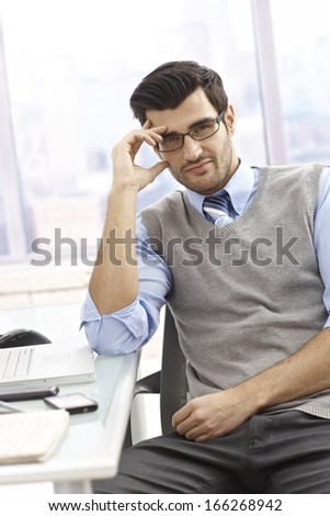 Portrait of casual office worker sitting at desk in bright office, smiling.