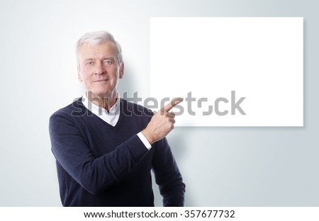 Portrait of casual old businessman standing at isolated background and showing with his finger to isolated white board. - stock photo