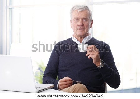 Portrait of casual senior businessman sitting at desk in front of laptop and drinking coffee while relaxing at office.