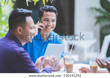 Portrait of casual three Business people meeting in cafe. one man calling by phone