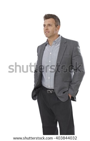 Portrait of casual young businessman standing hands in pockets, looking away. - stock photo
