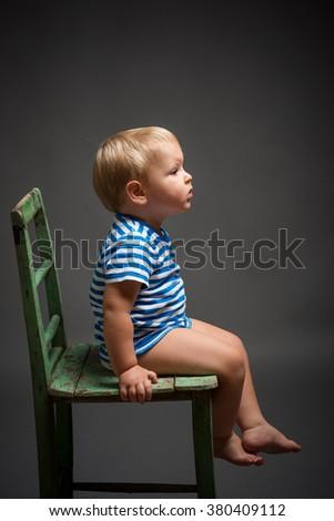 Portrait of caucasian boy in studio sittin on green vintage chair, gray background - stock photo