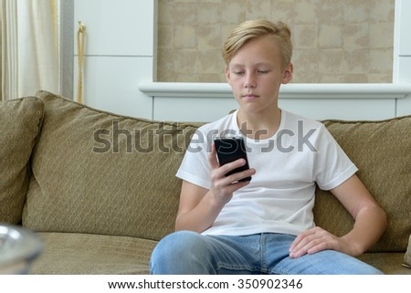 Portrait of Caucasian boy sitting on sofa and using mobile phone