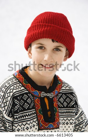 Portrait of Caucasian boy wearing sweater and red winter cap smiling at viewer.