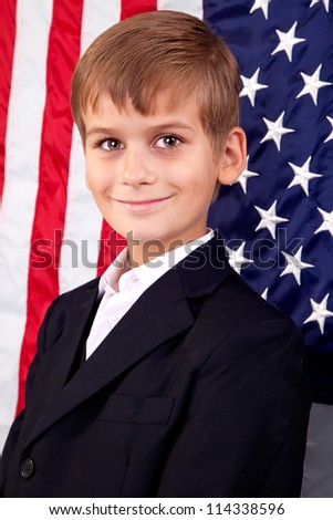 Portrait of Caucasian boy  with American flag in background. - stock photo