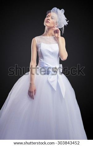 Portrait of Caucasian Bride Posing in Gorgeous Wedding Dress Made to Order. Against Black Background. Vertical Image Composition