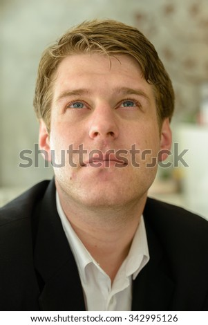 Portrait of Caucasian businessman sitting in coffee shop and looking up - stock photo