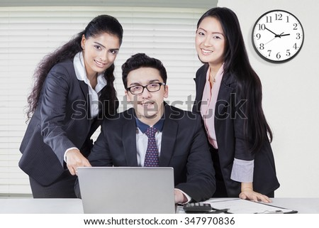 Portrait of caucasian businessman working with laptop and two female partners in the office - stock photo