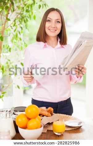 Portrait of caucasian businesswoman reading the newspaper while standing and having a cup of coffee - stock photo