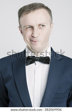 Portrait of Caucasian Handsome Man in Blue Suite Making Faces. Posing Against White. Vertical Image - stock photo