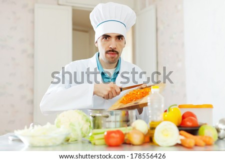 Portrait of  caucasian male cook with  vegetables at kitchen - stock photo