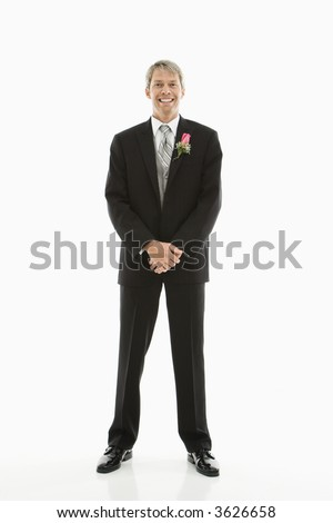 Portrait of Caucasian male in tuxedo with boutonniere. - stock photo