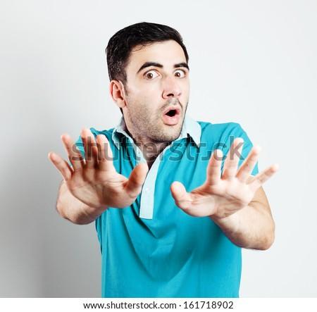 Portrait of caucasian male with blue shirt being scared in front of camera.Grey background - stock photo