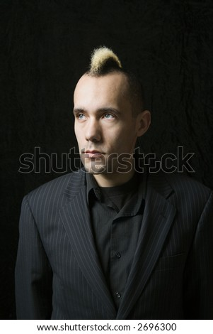 Portrait of Caucasian man in suit with mohawk against black background.