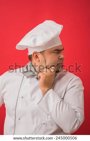 Portrait of caucasian man with chef uniform thinking - stock photo