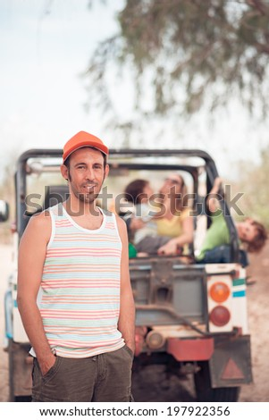 Portrait of Caucasian man with his family and an off-road car in the background - stock photo