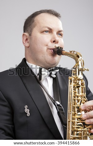 Portrait of Caucasian Player in Suit Playing on Saxophone.Vertical Image Composition - stock photo