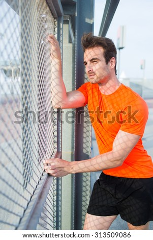 Portrait of caucasian sports man standing near metal fence thoughtful looking away while rest, young caucasian male runner taking break after active training with copy space area for text your message - stock photo
