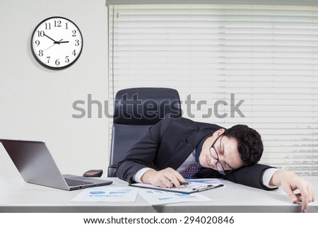 Portrait of caucasian worker with formal suit sleeping on desk in the office with a clock on the wall - stock photo