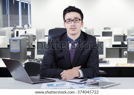 Portrait of caucasian young businessperson wearing formal suit in the office and looks confident, looking at the camera with laptop and document on desk - stock photo