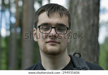 portrait of caucasian young man in glasses with a beard and a backpack on the background of the forest - stock photo