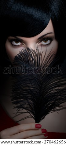 Portrait of charming brunette woman with smooth, silky hair in the darkness. Sensual lady mysteriously looks, covering her lips by black feather. Girl with fashionable bob hairstyle, red nails, makeup - stock photo