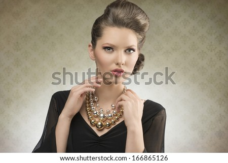 portrait of charming fashion lady posing with brown hair-style, elegant black dress and bright necklace     - stock photo