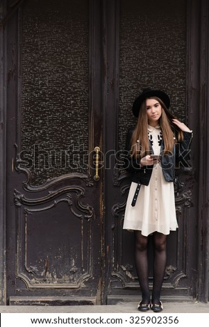 Portrait of charming female hipster with nice look wait for a call on cell telephone, attractive woman dressed in trendy clothes holding mobile phone while standing against retro door with copy space - stock photo