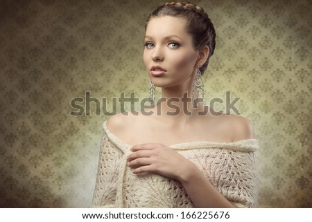 portrait of charming female with elegant style posing with classic hair-style, precious earrings and wool shawl     - stock photo