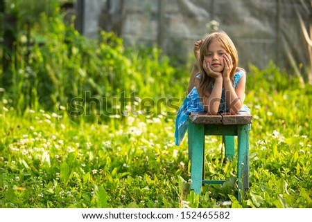 Portrait of charming little girl in the yard of a country house - stock photo