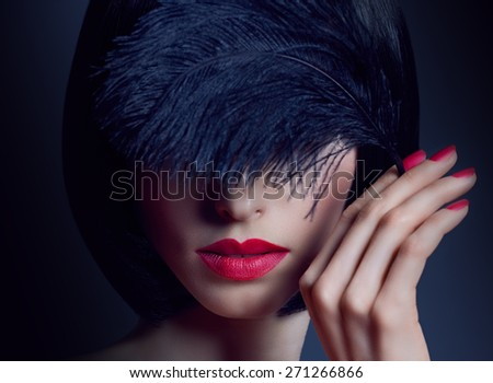 Portrait of charming nude brunette woman with smooth, silky hair in the darkness. Sensual lady covering her eyes by black feather. Girl with fashionable bob hairstyle, red nails and lipstick, makeup - stock photo