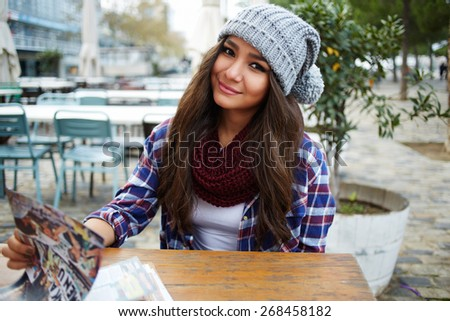 Portrait of charming pretty girl sitting at the table of beautiful coffee shop, attractive young woman with restaurant menu sitting on the terrace looking to you - stock photo