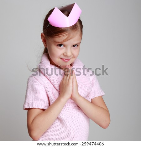 Portrait of charming smiling child in a pink knitted dress with a pink crown on his head on a gray background - stock photo