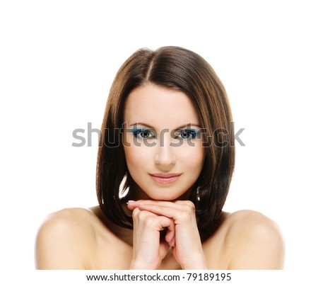 Portrait of charming smiling young woman with bared shoulders which touches fingers cheek, on white background. - stock photo