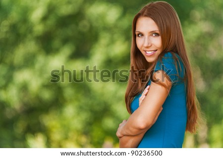 portrait of charming woman with long hair standing sideways with his arms folded across his chest and raising his shoulder background summer green park - stock photo