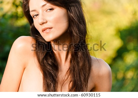 Portrait of charming woman with naked shoulders, against green foliage. - stock photo