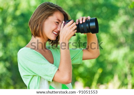 portrait of charming, young, beautiful, short-haired woman in profile, photographs, against background of summer, green, nature - stock photo