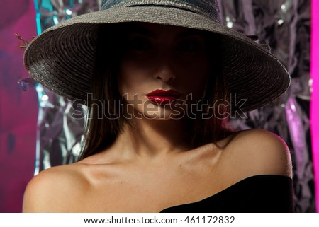 portrait of charming young caucasian woman in hat with wide brim and red lips posing in studio and looking at the camera