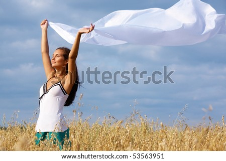Portrait of charming young girl raising her arms with chiffon shawl