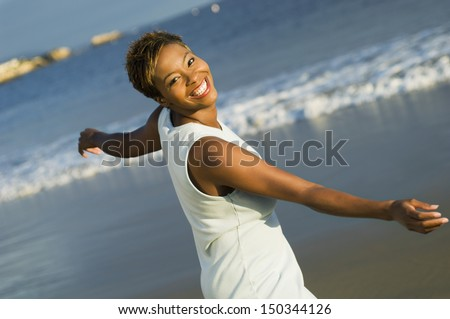 Portrait of cheerful African American woman enjoying vacation on beach - stock photo