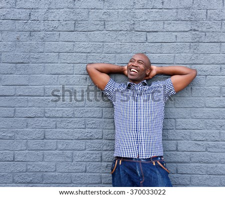 Portrait of cheerful african man standing with his hands behind head against a gray background - stock photo