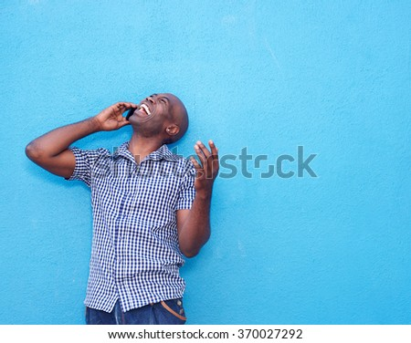 Portrait of cheerful african man talking on mobile phone  - stock photo