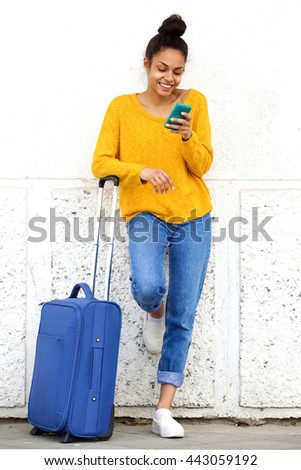 Portrait of cheerful african woman reading text message mobile phone and standing outside with suitcase - stock photo