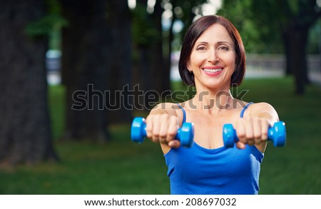 Portrait of cheerful aged woman in fitness wear exercising with dumbbells in park. - stock photo